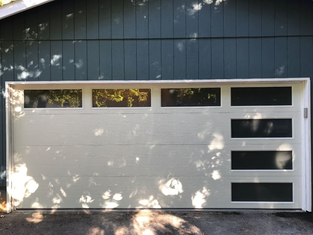 White garage door with windows on a blue house