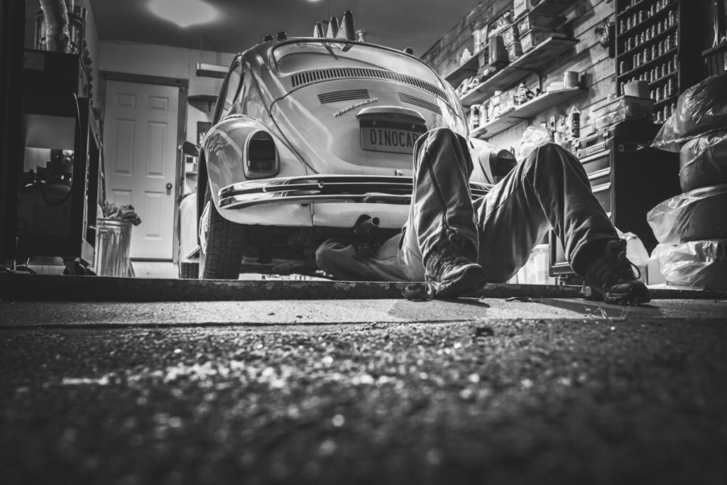 Guy working on a VW bug in his garage