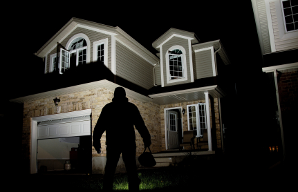 A thief in front of a home at night